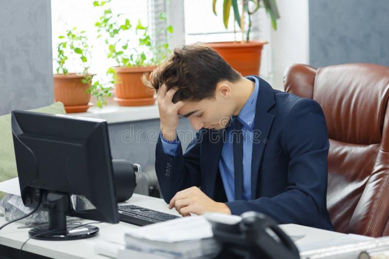 年轻沮丧与研究计算机的问题年轻商人在办公室 库存图片