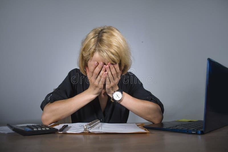 年轻沮丧和被注重的女商人哭泣哀伤在办公桌与文书工作workl淹没的便携式计算机一起使用 免版税库存照片