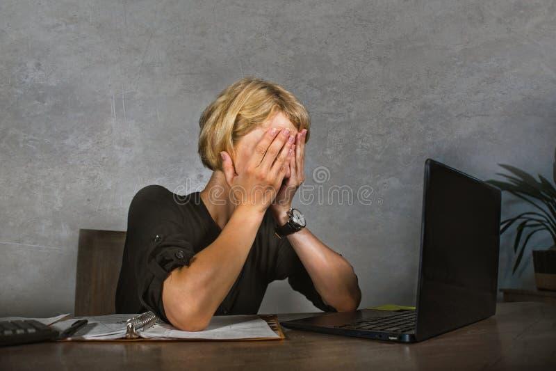 年轻沮丧和被注重的女商人哭泣哀伤在办公桌与文书工作workl淹没的便携式计算机一起使用 库存照片