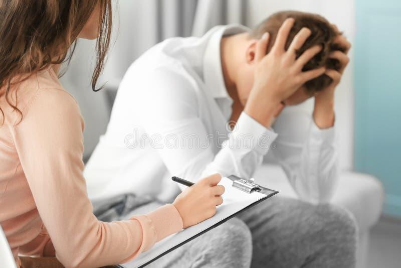 年轻沮丧的人在医生` s办公室 库存照片