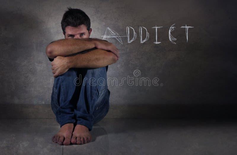 年轻沮丧的在药物赌博的互联网和酒瘾问题概念的人遭受的消沉 免版税库存图片