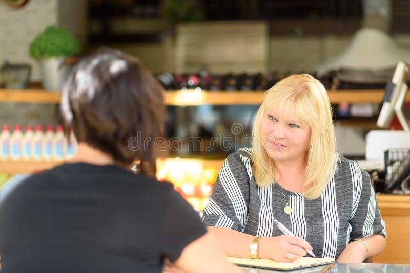 年轻沮丧的妇女谈话与夫人心理学家在会议,精神健康期间 库存图片