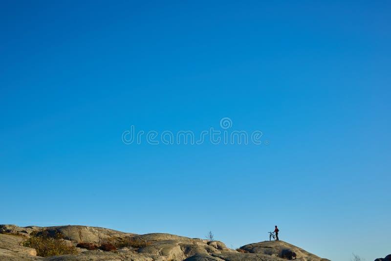 年轻活跃人剪影有今后站立和注视着山全景背景的自行车的 图库摄影