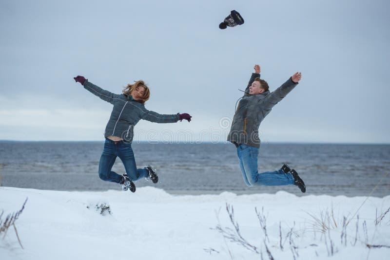 年轻活跃夫妇快乐一起跳跃上流在寒假海滩,自然户外 消遣乐趣的能量 免版税库存照片