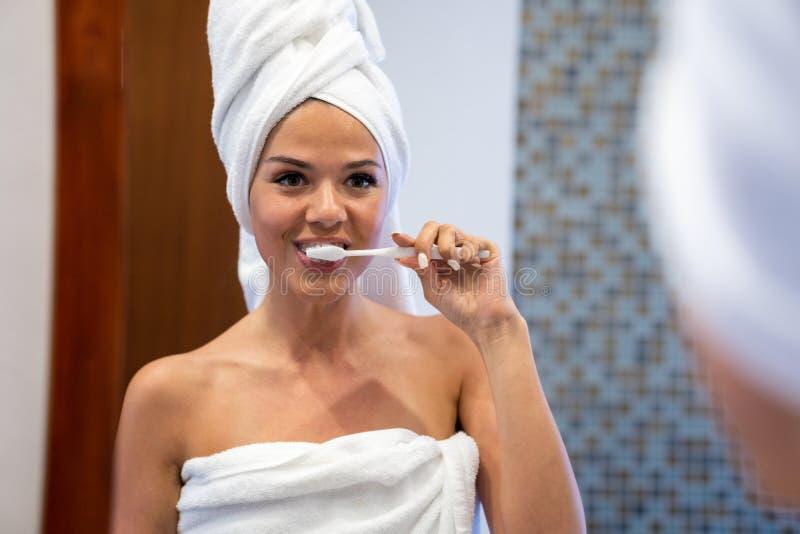 年轻浅黑肤色的男人看并且清洗牙 女孩s头和身体在白色毛巾打扮 库存照片