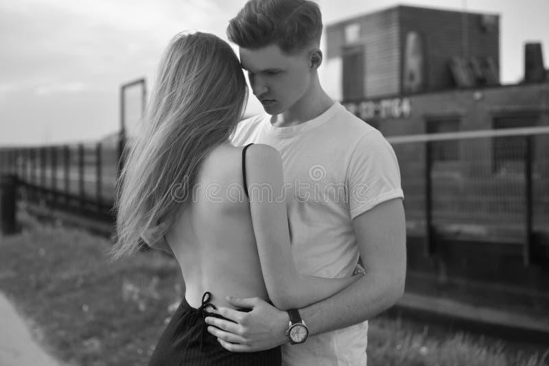 年轻浪漫夫妇特写镜头是亲吻和享受公司彼此在黑白 耦合爱年轻人 免版税库存照片