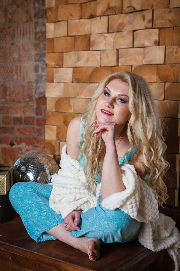 年轻浪漫妇女坐砖背景 免版税库存图片