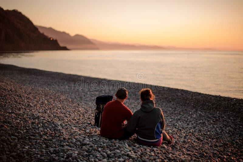 年轻浪漫愉快的夫妇坐海滩 免版税库存照片