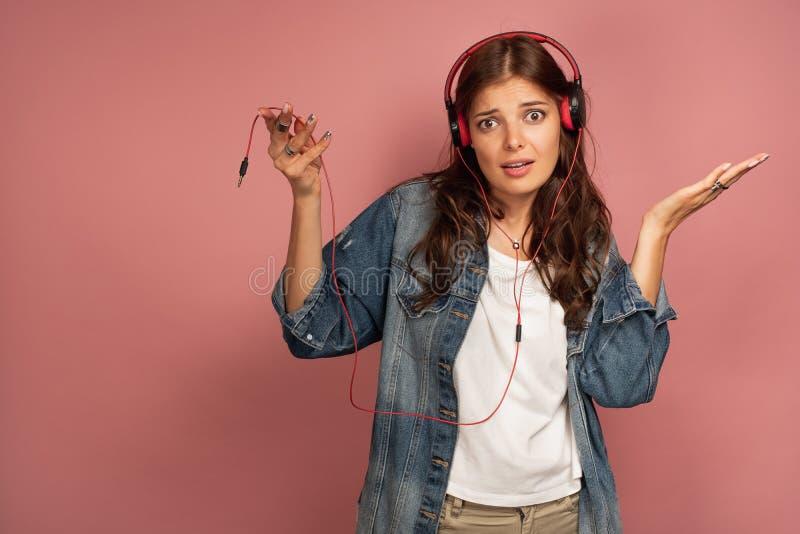 年轻深色头发的迷茫的妇女传播她实施作为她的耳机没有被连接到音乐设备,桃红色 免版税图库摄影