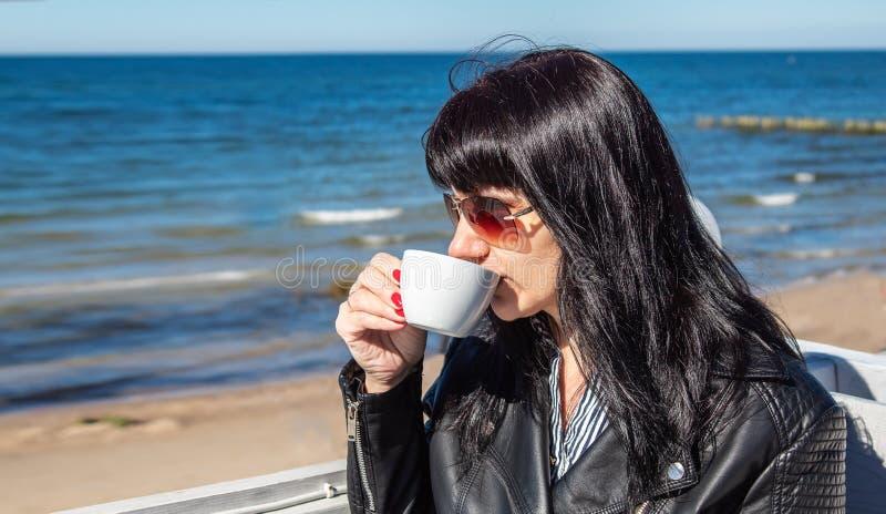 年轻深色的在一个室外咖啡馆的妇女饮用的咖啡在海附近 免版税库存照片