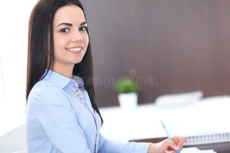 年轻深色的女商人看起来工作在办公室的学生女孩 西班牙或拉丁美洲的女孩愉快在工作 图库摄影