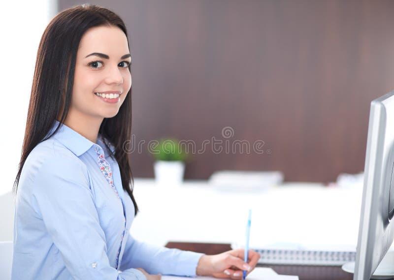 年轻深色的女商人看起来工作在办公室的学生女孩 西班牙或拉丁美洲的女孩愉快在工作 库存照片
