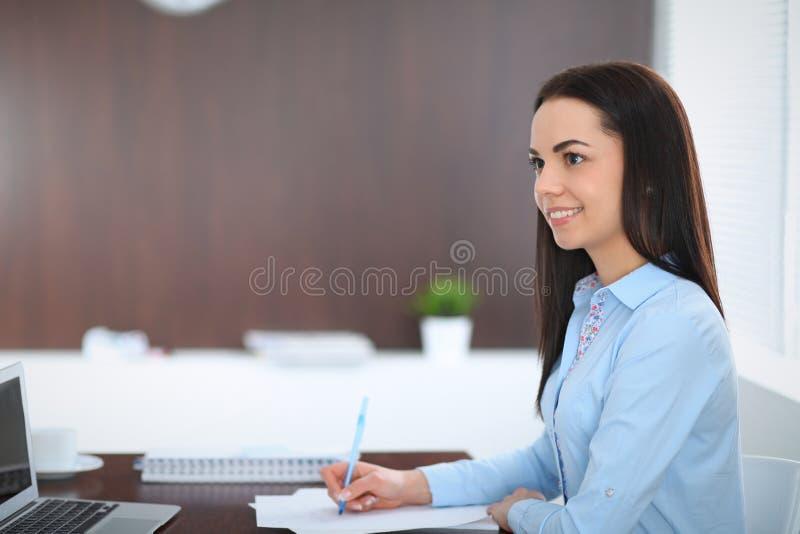 年轻深色的女商人看起来工作在办公室的学生女孩 西班牙或拉丁美洲的女孩身分 免版税库存图片