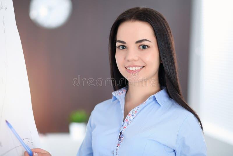 年轻深色的女商人看起来工作在办公室的学生女孩 西班牙或拉丁美洲的女孩身分 免版税库存照片