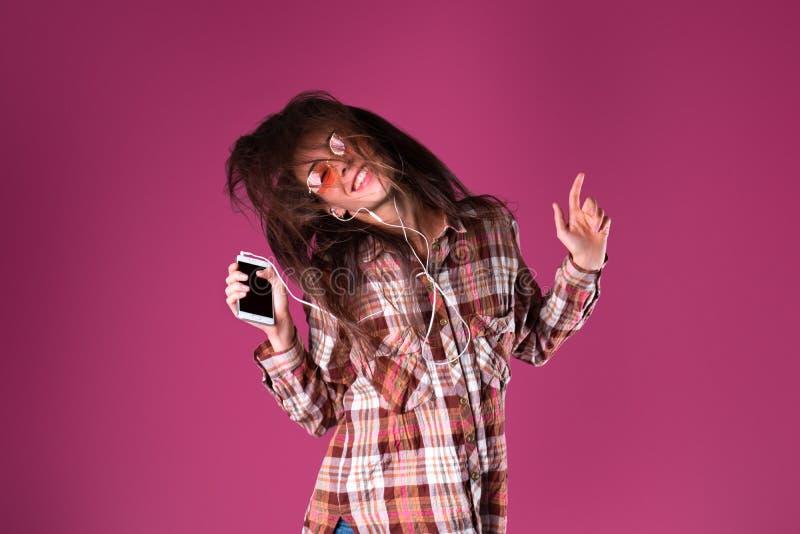 年轻深色的女孩音乐上瘾者听到在智能手机的音乐有耳朵电话的 库存图片