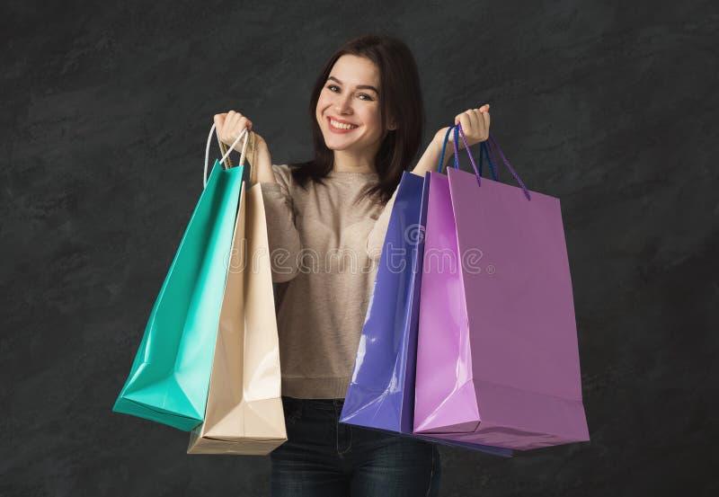 年轻深色的妇女的图片有购物袋的 免版税库存照片