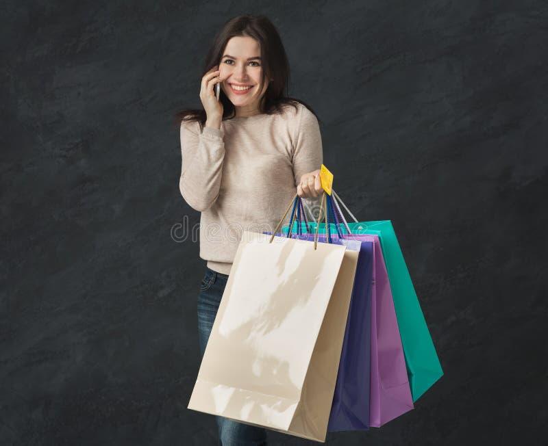 年轻深色的妇女的图片有购物袋的 库存图片