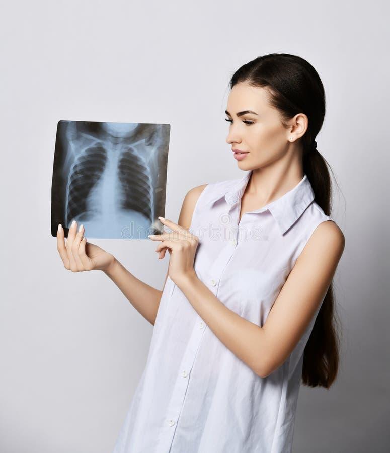 年轻深色的妇女看肺她在灰色握胸口的X光检查 免版税库存照片