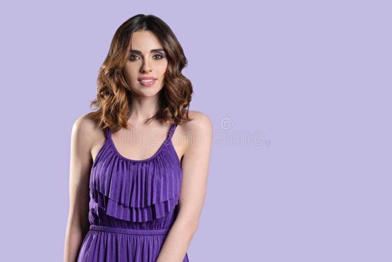 年轻深色的妇女秀丽画象有波浪发和构成的,在紫色背景的紫色礼服,复制空间 免版税图库摄影