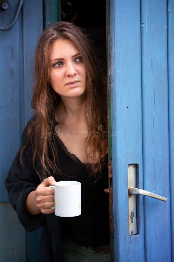 年轻深色的妇女藏品杯子和站立在蓝色门 库存图片