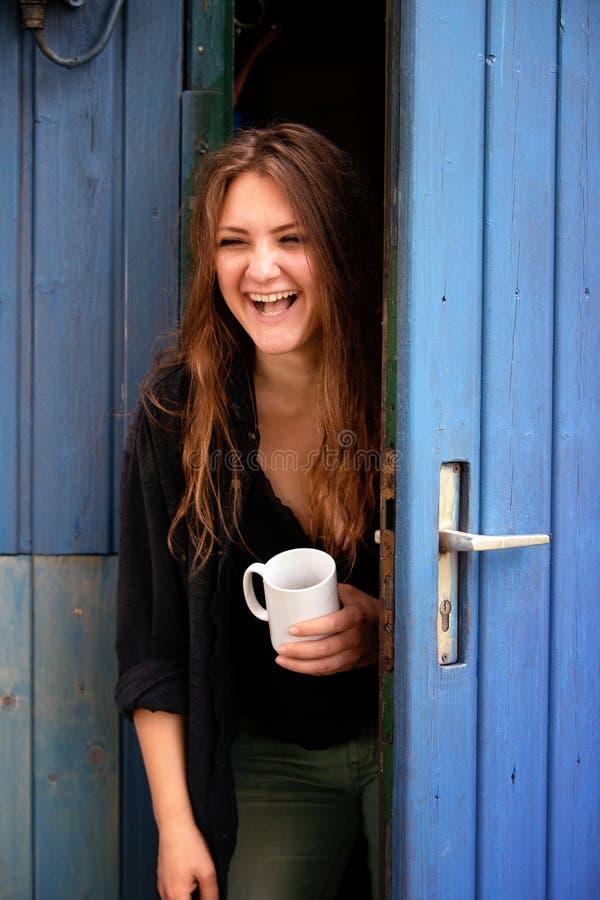 年轻深色的妇女藏品杯子和站立在蓝色门 库存照片
