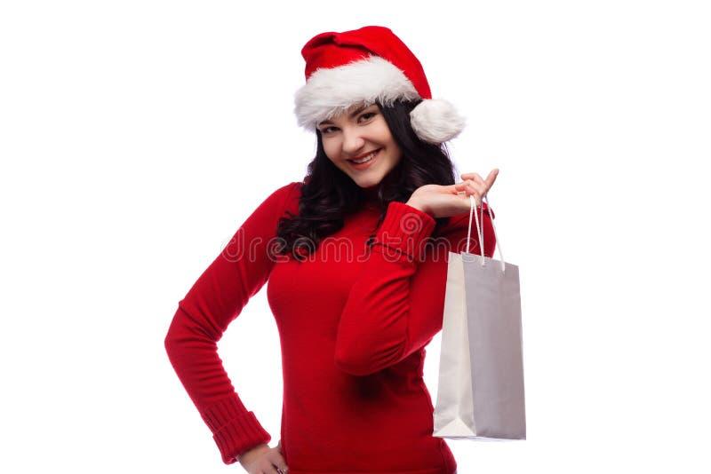 年轻深色的拿着与一张愉快的面孔的妇女佩带的圣诞节帽子当前袋子 查出 免版税库存照片