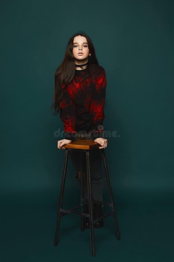 年轻深色的青少年的女孩在深绿背景的椅子附近站立,隔绝在演播室 库存照片