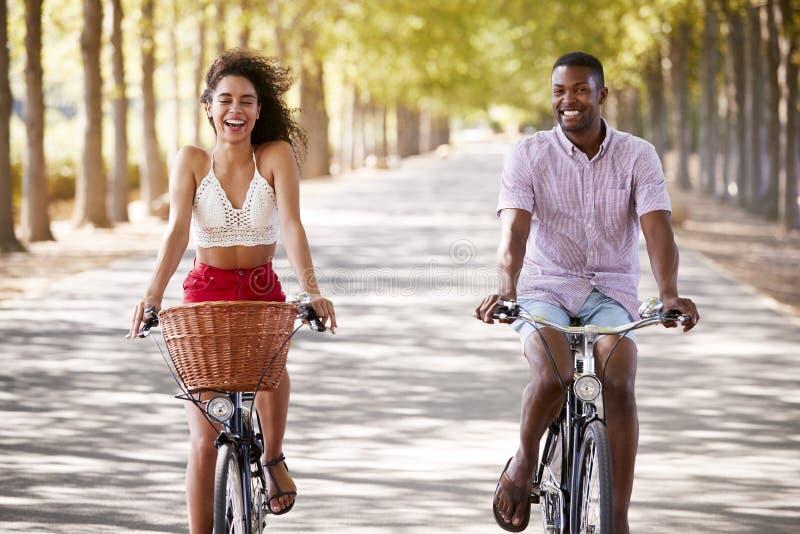 年轻混合的族种夫妇骑马在树被排行的路骑自行车 免版税库存照片