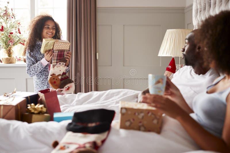 年轻混合的族种女孩运载的礼物在她的parentsï ¿ ½卧室在圣诞节早晨,坐在床,关闭上的父母  免版税库存图片