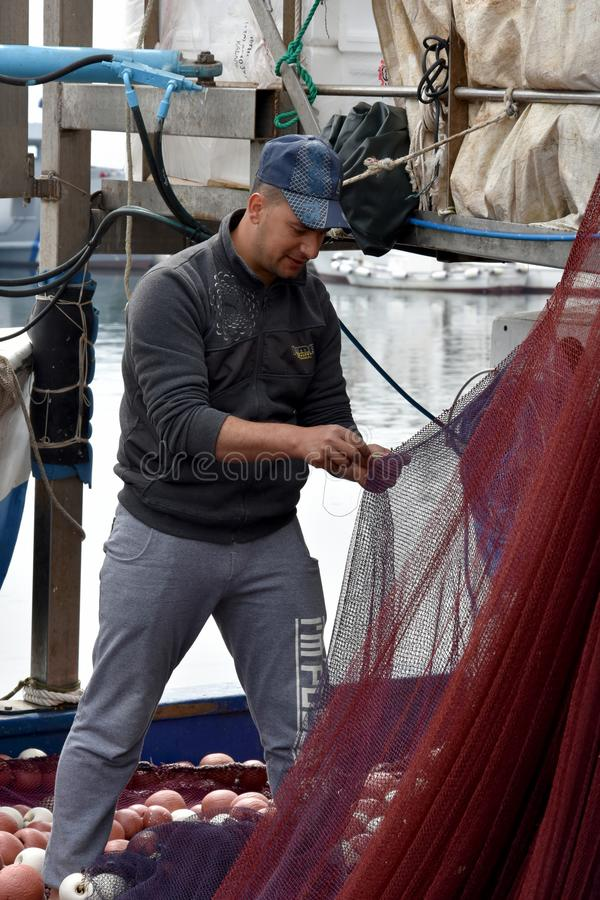 年轻渔夫修补工作网 免版税图库摄影