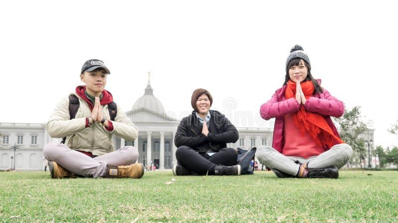年轻游人坐和在赤眉军博物馆前面的姿势 库存图片