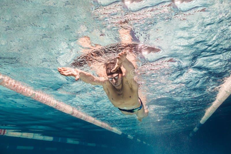 年轻游泳者的水下的图片盖帽和风镜训练的 库存图片