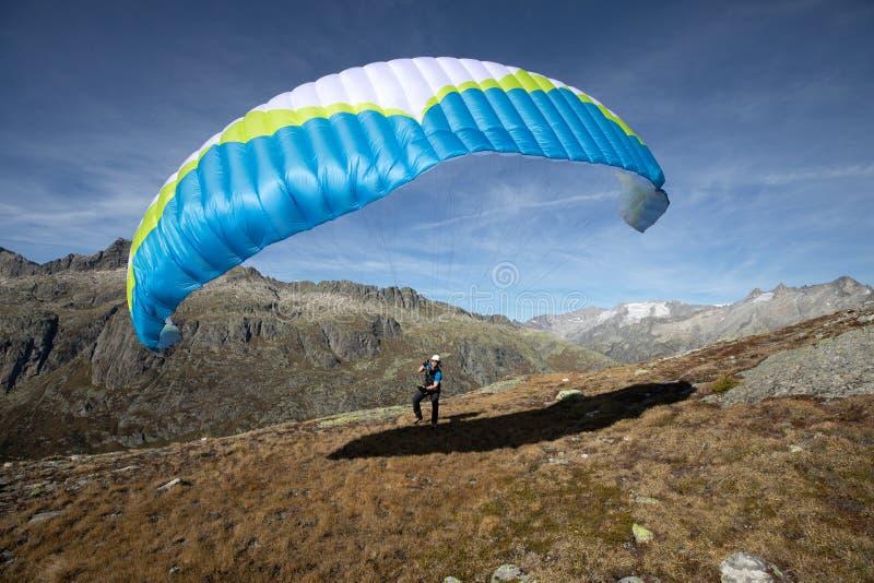 年轻滑翔伞飞行员在瑞士阿尔卑斯山脉,所谓的地面工作使用他的滑翔伞使用与风 免版税图库摄影