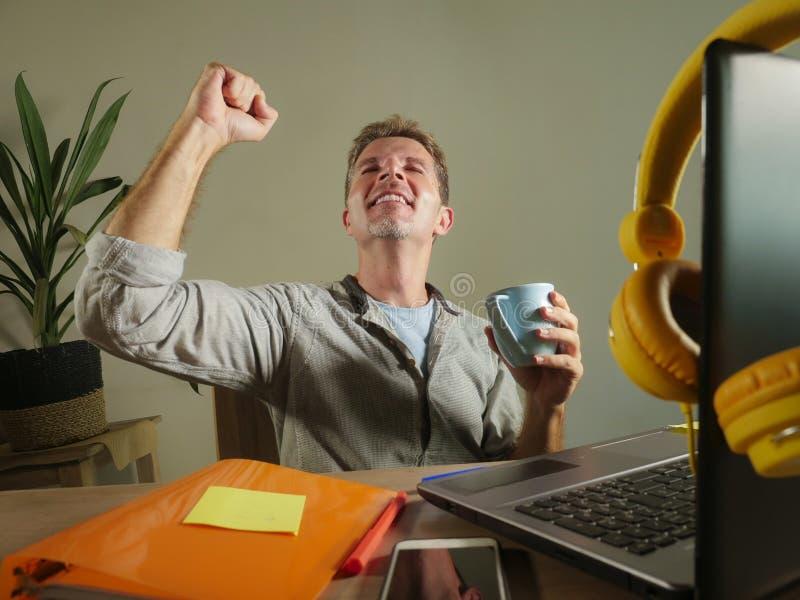 年轻满意和确信的商人激发打手势在胜利作为在家工作有便携式计算机的优胜者办公室  库存图片