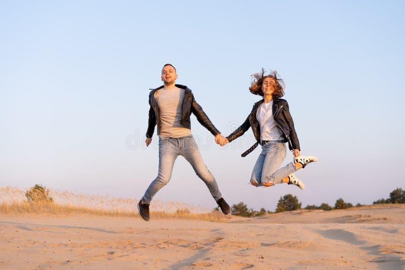 年轻漂亮的白种人夫妇在沙滩上手牵手 免版税库存照片