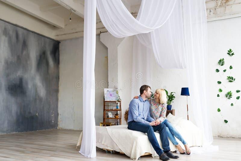 年轻爱恋的夫妇坐床,亲吻和拥抱 库存照片