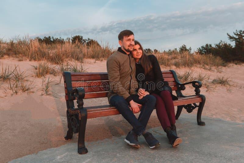 年轻爱恋的夫妇坐长凳在海岸附近在秋天 库存图片