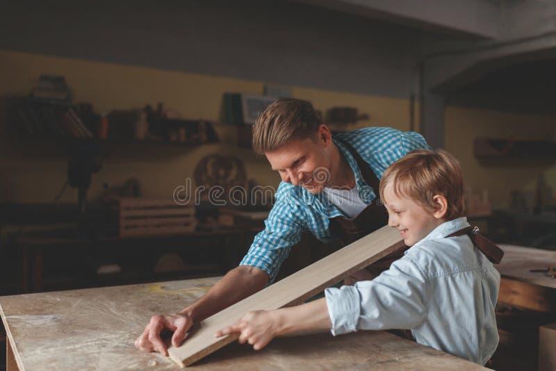 年轻父亲和一个小儿子在工作 库存图片