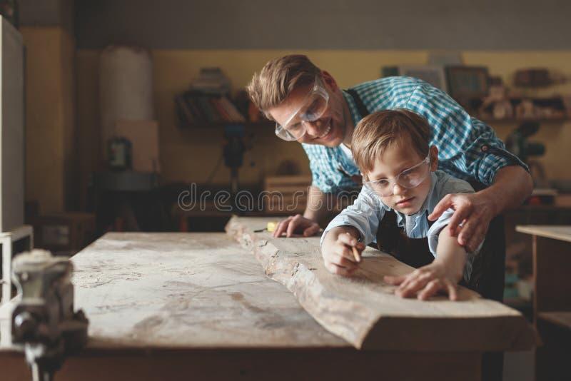 年轻父亲和儿子在工作 库存照片