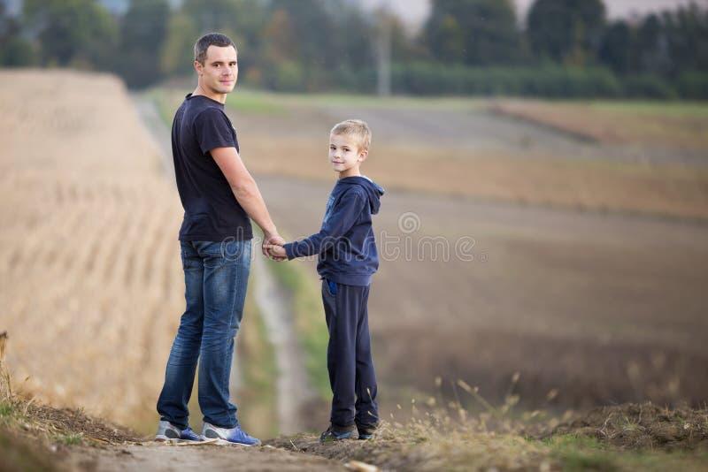 年轻父亲和微笑的逗人喜爱的儿童男孩身分在握手在被弄脏的有雾的草甸和绿色树背景的象草的领域 免版税库存照片