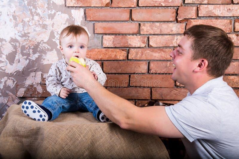 年轻父亲给他的儿子一个绿色苹果吃 在红砖墙壁背景 牛仔裤坐的一个年婴孩 免版税库存照片