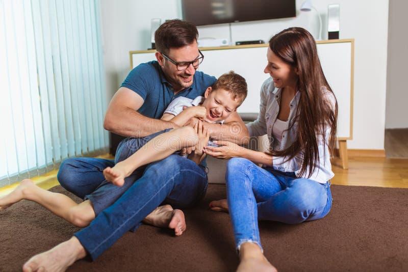 年轻父母和他们的孩子是非常愉快的,他们在家是 库存照片