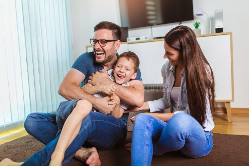 年轻父母和他们的孩子是非常愉快的,他们在家是 库存图片