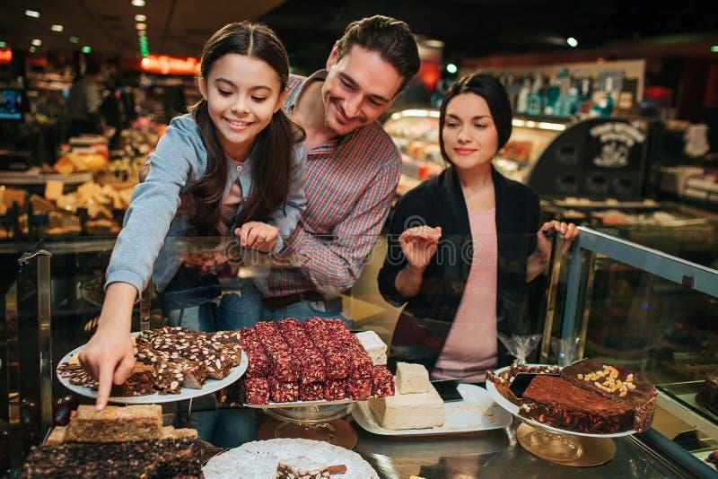 年轻父母和女儿在杂货店 女孩对甜点的伸手可及的距离手 可口鲜美糖果 父亲拿着她 库存图片