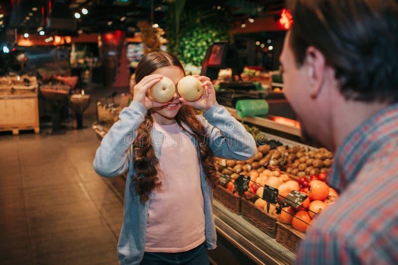 年轻父母和女儿在杂货店 她用苹果和微笑盖眼睛 父亲看看她 滑稽嬉戏 免版税库存图片