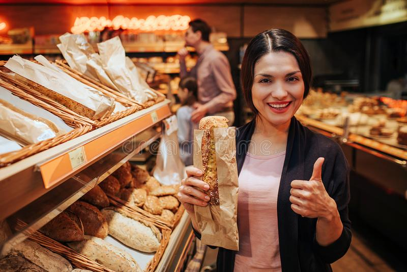 年轻父母和女儿在杂货店 正面快乐的妇女举行面包在手和展示大赞许上 Fathr 库存照片