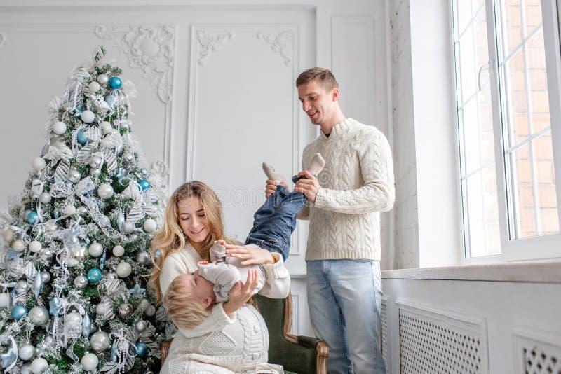 年轻父母无所事事并且使用与一点儿子 愉快系列的乐趣有家庭 在明亮的生活的圣诞节早晨 免版税库存图片
