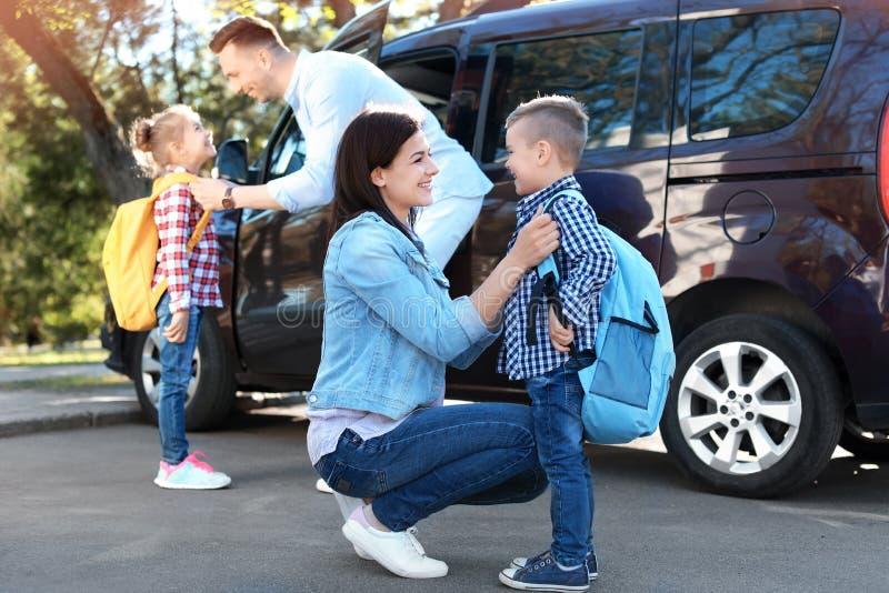 年轻父母说再见向他们的孩子临近学校 库存照片