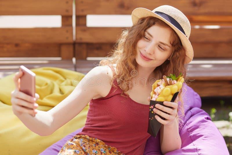 年轻狡猾的头发的妇女室外水平的照片在镇公园时做selfie,当坐温和的frameless椅子,戴帽子, 免版税图库摄影