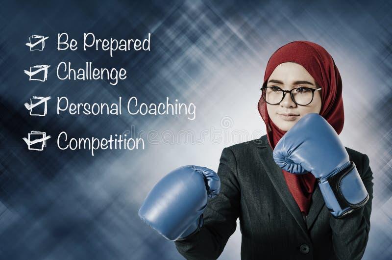 年轻猛击对成功的女实业家佩带的拳击手套 库存图片